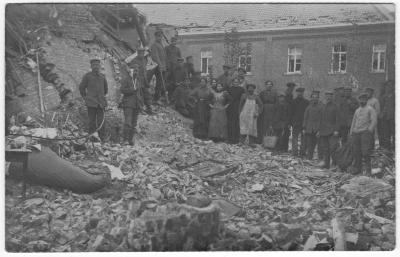 Mensen poseren bij gebouw in puin na bombardement, wellicht deel van klooster