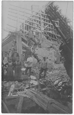 Mensen poseren bij huis in puin na bombardement