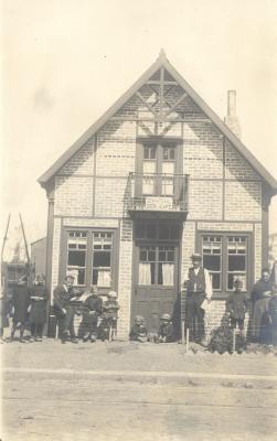 Familiefoto bij huis met opschrift: 'De Wahtzaal, Bier, Kafé', Dadizele