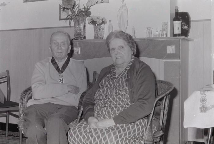 Bejaard echtpaar poseert in woonkamer