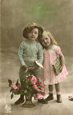 Beeldzijde kerst- en nieuwjaarskaart, jongen en meisje met korf bloemen