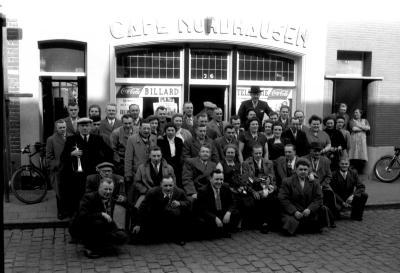 Groepsfoto voor café Nordhausen, man met weekbode, Izegem 1957