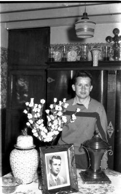 Wielrenner Pol Rosseel poseert in kamer bij foto, beker en bloemen, Izegem 1957