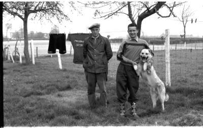Wielrenner Pol Rosseel poseert in tuin met supporter en met hond, Izegem 1957
