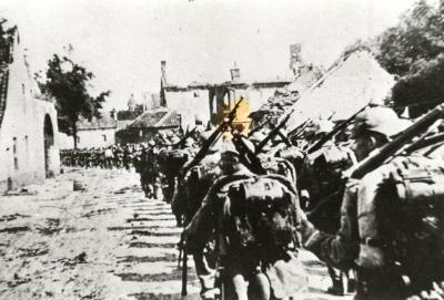 Duitse soldaten marcheren langs vernielde huizen