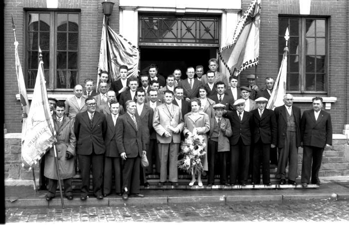 Kampioenviering vinkenzetters: Groepsfoto vinkenzetters  aan gemeentehuis, Emelgem 18-08-1957