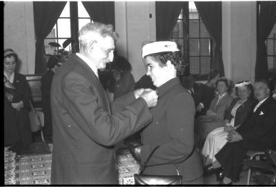 Huldiging gedecoreerden Unions: burgemeester speldt het ereteken op bij een mevrouw, Izegem 1957