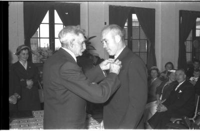 Huldiging gedecoreerden Unions: burgemeester speldt het ereteken op bij een mijnheer, Izegem 1957
