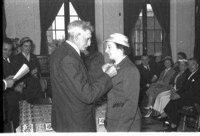 Huldiging gedecoreerden Unions: burgemeester speldt het ereteken op bij mevrouw J. Remmerie, Izegem 1957
