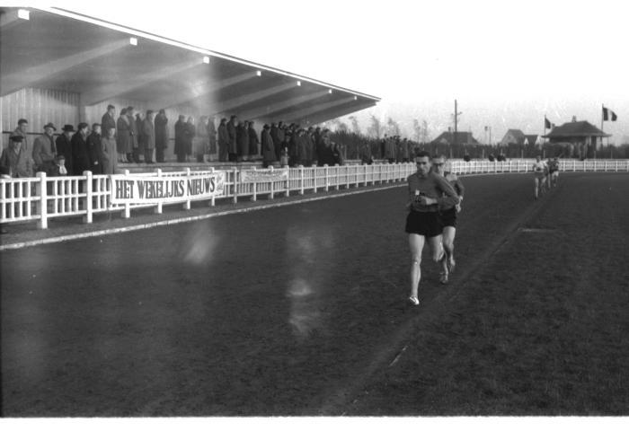 Fotoreportage atletiekwedstrijd: Herman en Leenaert lopen voorbij de tribune, Izegem 1957