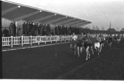 Fotoreportage atletiekwedstrijd: atleten lopen voorbij tribune, Izegem 1957