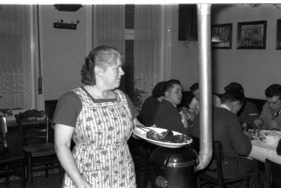 Kampioenviering boogschutters café 'Stad Kortrijk': feesttafel bij kachel, Izegem 1957