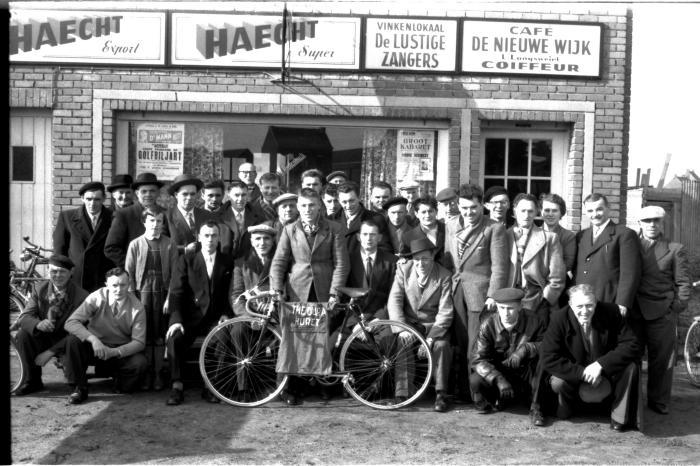 Café 'De Nieuwe Wijk, L. Langsweirt, Coiffeur': groepsfoto, Emelgem 1958